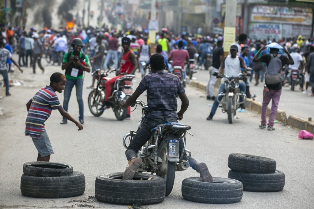 A motorcyclist uses his feet to drag tires into place for a barricade during a protest to demand the resignation of President Jovenel Moise in Port-au...