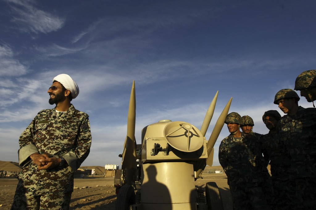 FILE - In this Nov. 13, 2012 file photo, an Iranian clergyman stands next to missiles and army troops, during a manoeuvre, in an undisclosed location ...