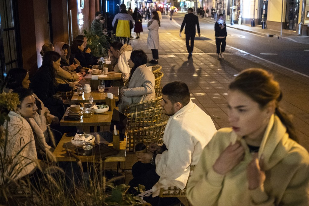 Customers sit outside a restaurant at Patriarshiye Prudy, a hip restaurant and bar district in Moscow, Russia, late Friday, Oct. 16, 2020. The outbrea...