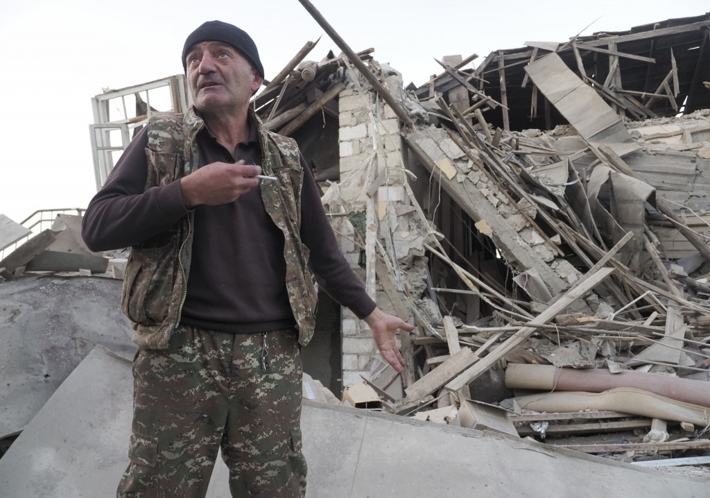 A man stands near his neighbour's house destroyed by shelling by Azerbaijan's artillery during a military conflict in Stepanakert, the separatist regi...
