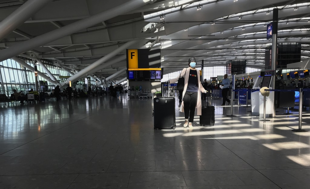 FILE - In this Tuesday, March 24, 2020 file photo, a woman wears a mask as she walks through a quieter than usual Heathrow Airport Terminal 5, in Lond...