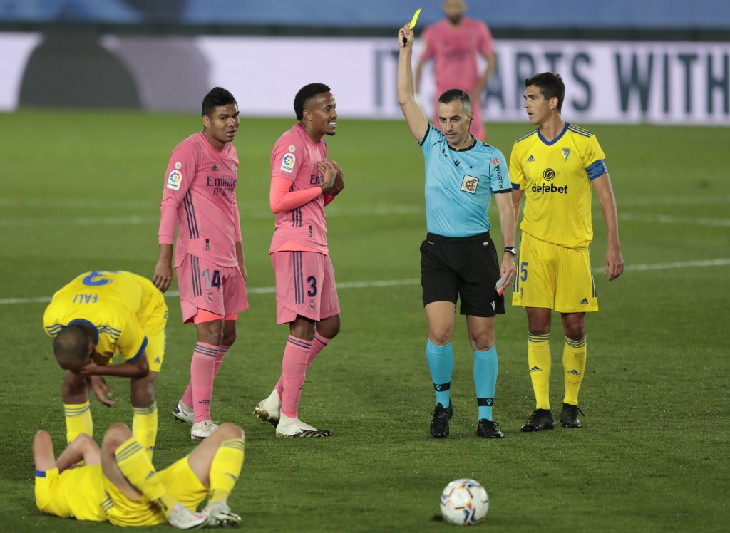 Real Madrid's Eder Militao, center, gets yellow cardduring the Spanish La Liga soccer match between Real Madrid and Cadiz at the Alfredo di Stefano st...