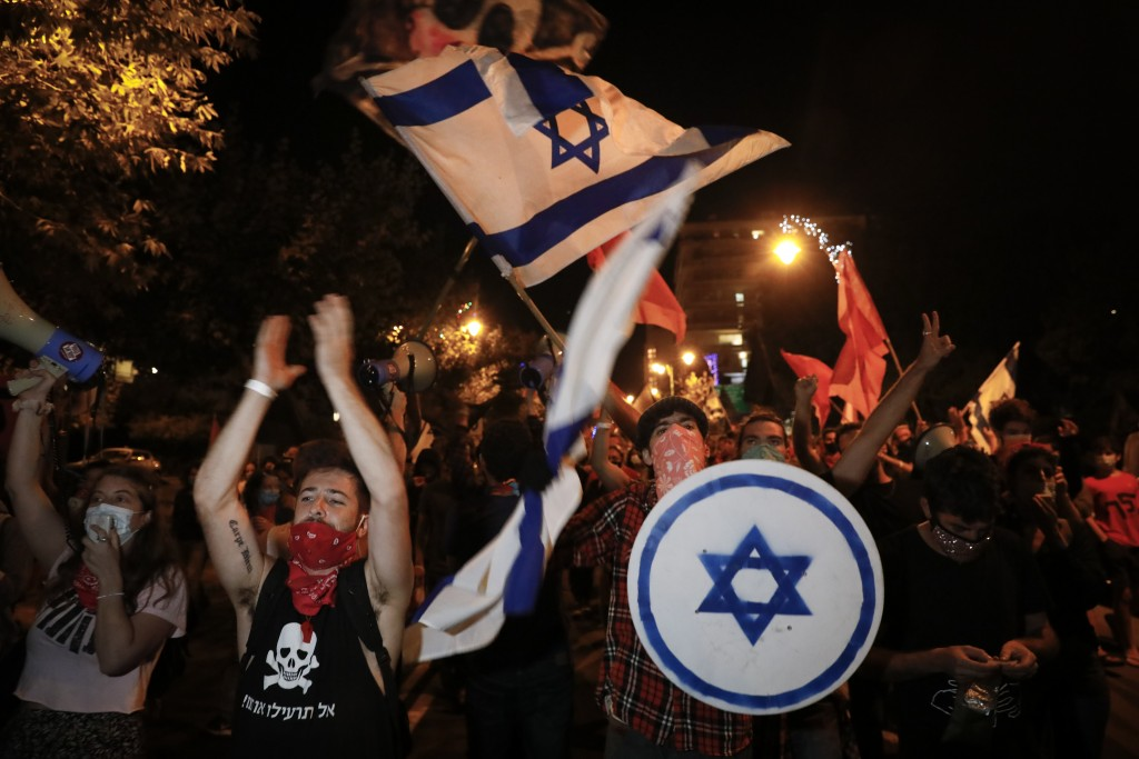 Protesters chant slogans and wave the Israeli national flag during a protest against Israel's Prime Minister Benjamin Netanyahu outside his residence ...