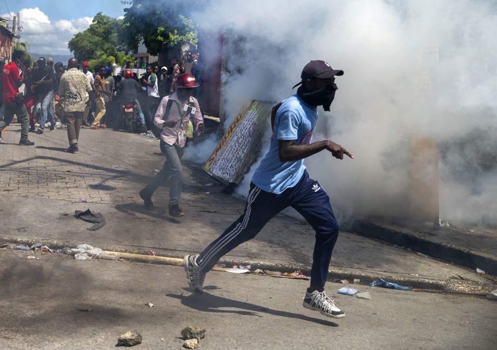 Protesters run from tear gas launched by police to disperse protesters demanding the resignation of President Jovenel Moise in Port-au-Prince, Haiti, ...