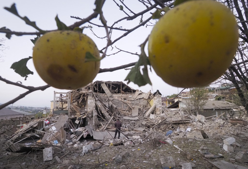 A man stands near a house destroyed by shelling from Azerbaijan's artillery during a military conflict in Stepanakert, the separatist region of Nagorn...