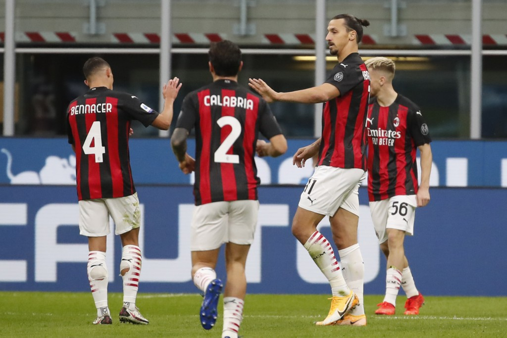 AC Milan's Zlatan Ibrahimovic celebrates with teammates keeping a safety distance after scoring his side's second goal during the Serie A soccer match...