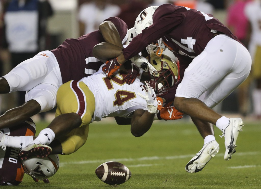 Boston College Running back Pat Garwo III, center, fumbles the ball while being tackled by Virginia Tech defenders Divine Deablo, left, and Devin Tayl...