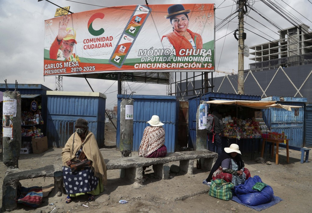 A billboard promoting presidential candidate Carlos Mesa of the Citizen Community political party towers over a trio of women in Rio Seco, Bolivia, Sa...