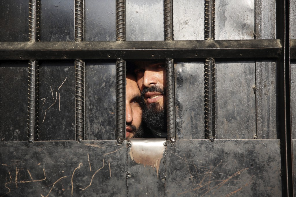 In this Monday, Aug. 3, 2020 file photo, Taliban prisoners watch through the door inside the prison after an attack in the city of Jalalabad, east of ...