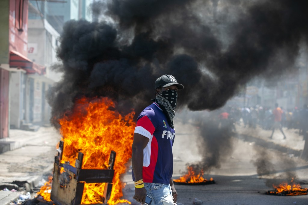 A protester walks past burning barricades during a protest demanding the resignation of President Jovenel Moise in Port-au-Prince, Haiti, Saturday, Oc...