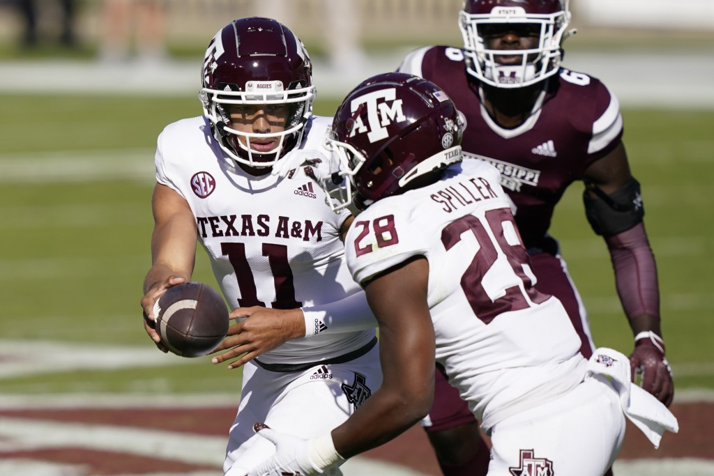 Texas A&M quarterback Kellen Mond (11) hands off to running back Isaiah Spiller (28) during the first half of an NCAA college football game against Mi...