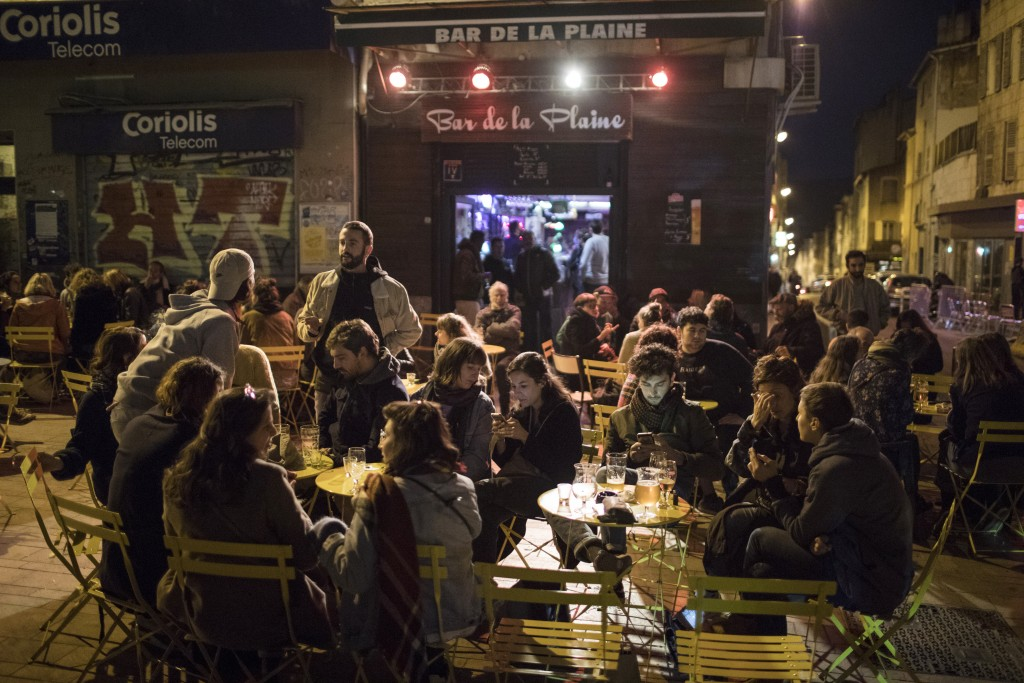 Friends gather at a bar before curfew in Marseille, southern France, Saturday, Oct. 17, 2020. France is deploying 12,000 police officers to enforce a ...