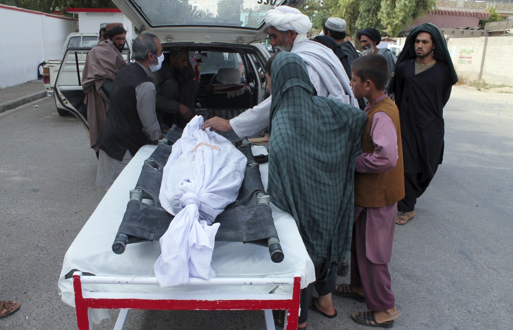 File - In this Monday, June 29, 2020 file photo, Afghans put the body of a man who was killed during a an attack in the southern Helmand province.Afgh...
