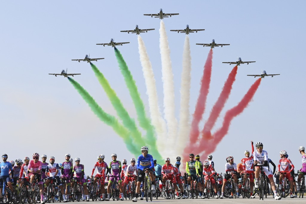 The pack of cyclists is backdropped by the Frecce Tricolori Italian Air Force aerobatic squad flying past, prior to the 15th stage of the Giro d'Itali...