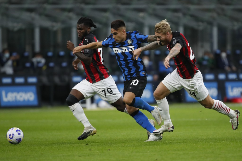 Inter Milan's Lautaro Martinez is cought in between AC Milan's Franck Kessie, left, and AC Milan's Simon Kjaer, during the Serie A soccer match betwee...