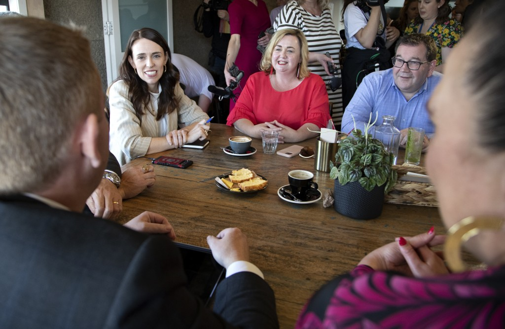 New Zealand Prime Minister Jacinda Ardern, left, talks with colleagues at a cafe in Auckland, New Zealand, Sunday, Oct. 18, 2020. Ardern has won a sec...