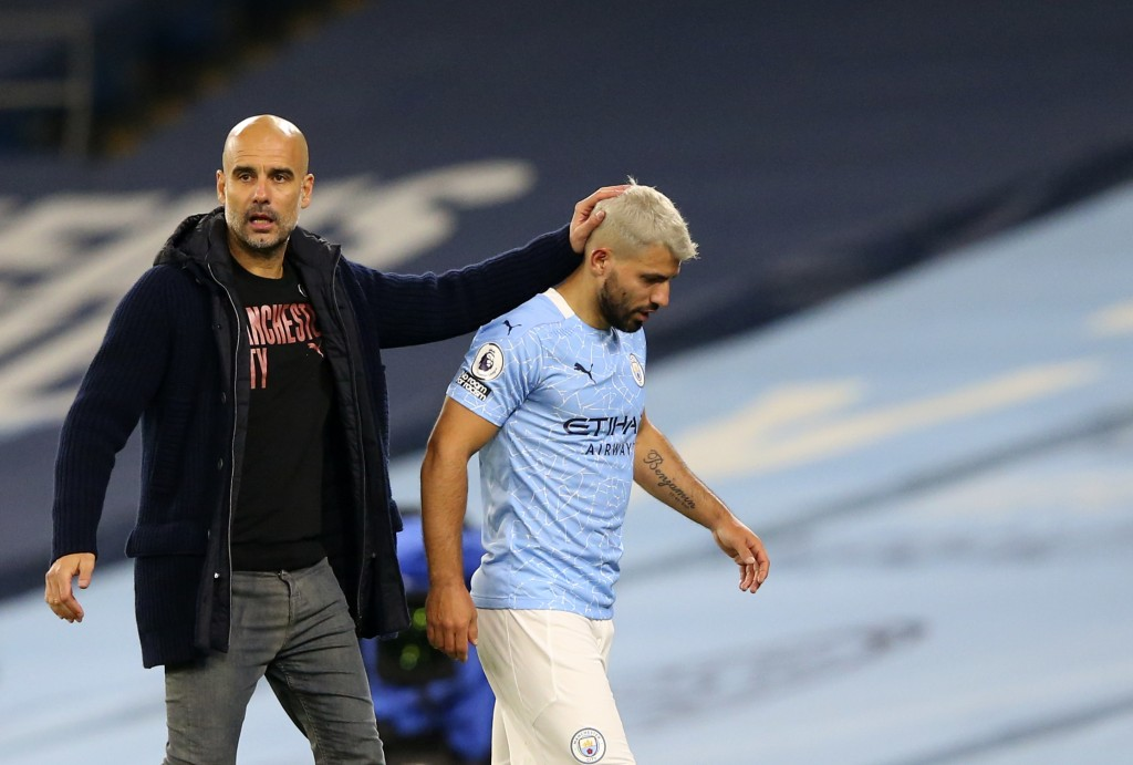 Manchester City's Sergio Aguero passes by Manchester City's head coach Pep Guardiola after being substituted during the English Premier League soccer ...