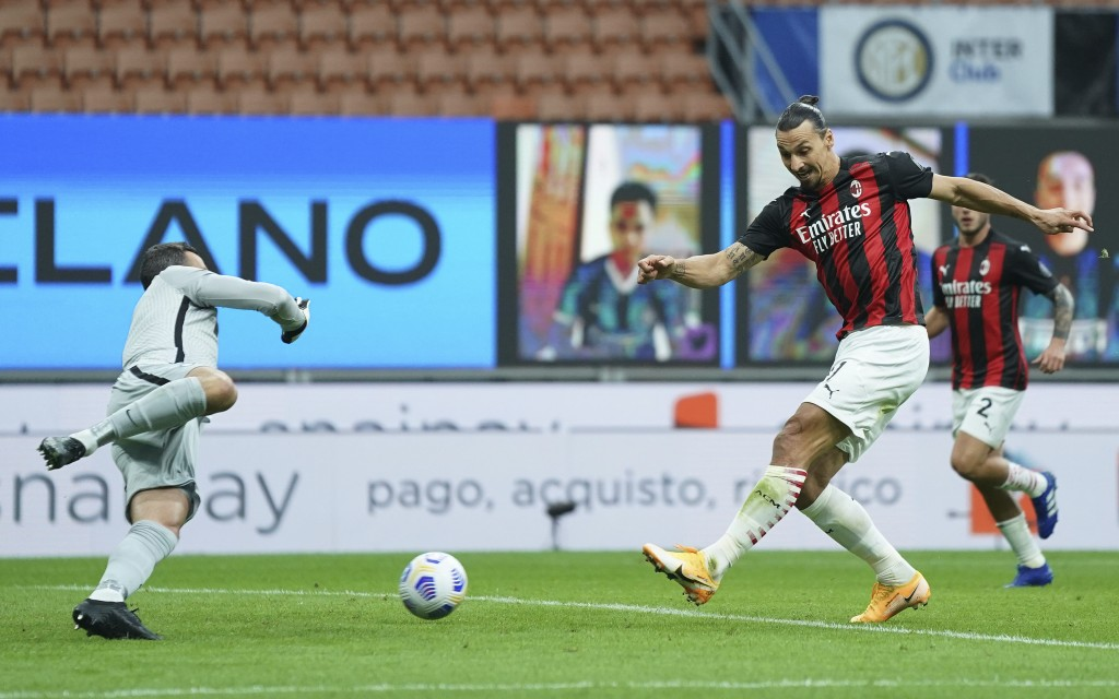 AC Milan's Zlatan Ibrahimovic scores his side's first goal during the Serie A soccer match between Inter Milan and AC Milan at the San Siro Stadium, i...
