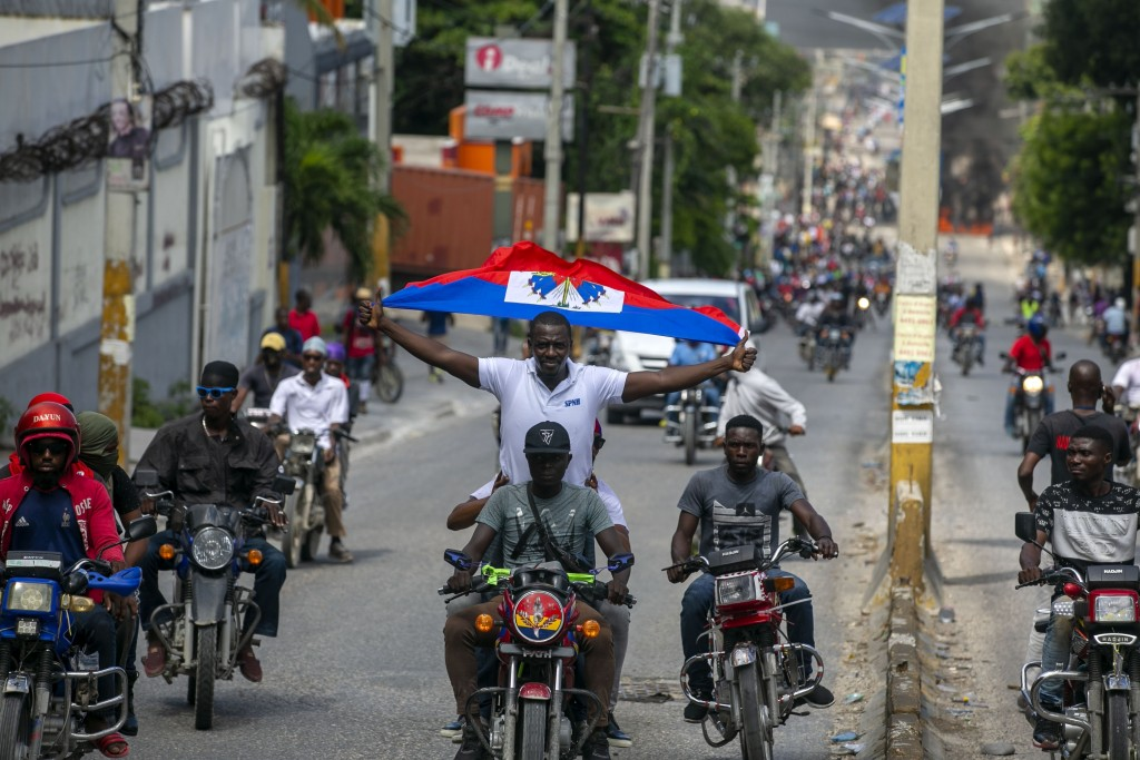 A protester holds up a Haitian national while riding on a motorcycle during a protest to demand the resignation of President Jovenel Moise in Port-au-...