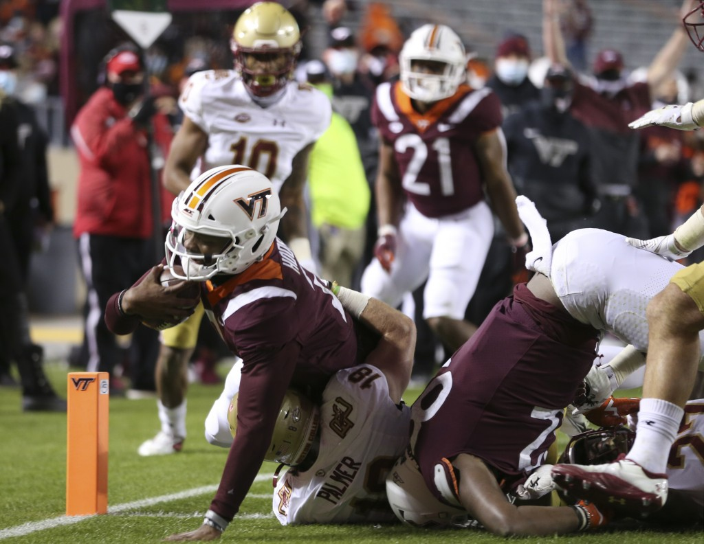 Virginia Tech quarterback Hendon Hooker, left, scores in the first half of an NCAA college football game against Boston College in Blacksburg Va. Satu...