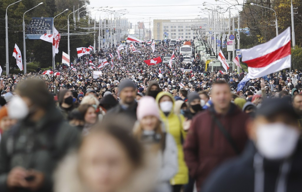 People with old Belarusian national flags march during an opposition rally to protest the official presidential election results in Minsk, Belarus, Su...