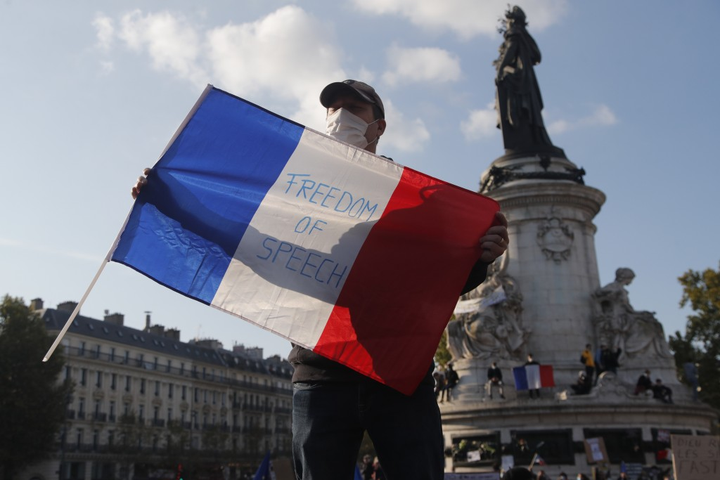 """A demonstrator holds a French flag with the slogan """"Freedom of Speech"""" during a demonstration Sunday Oct. 18, 2020 in Paris. Demonstrations around Fra..."""
