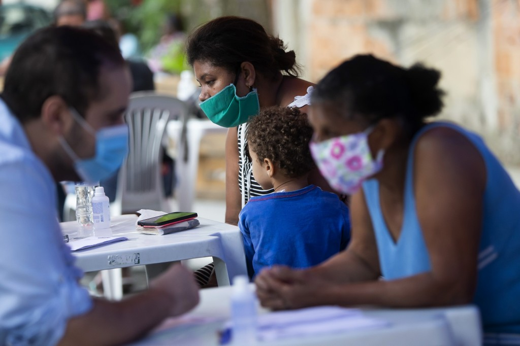 Residents receive medical attention during a campaign organized by doctors and volunteers amid the new coronavirus pandemic in the Chapadao favela in ...