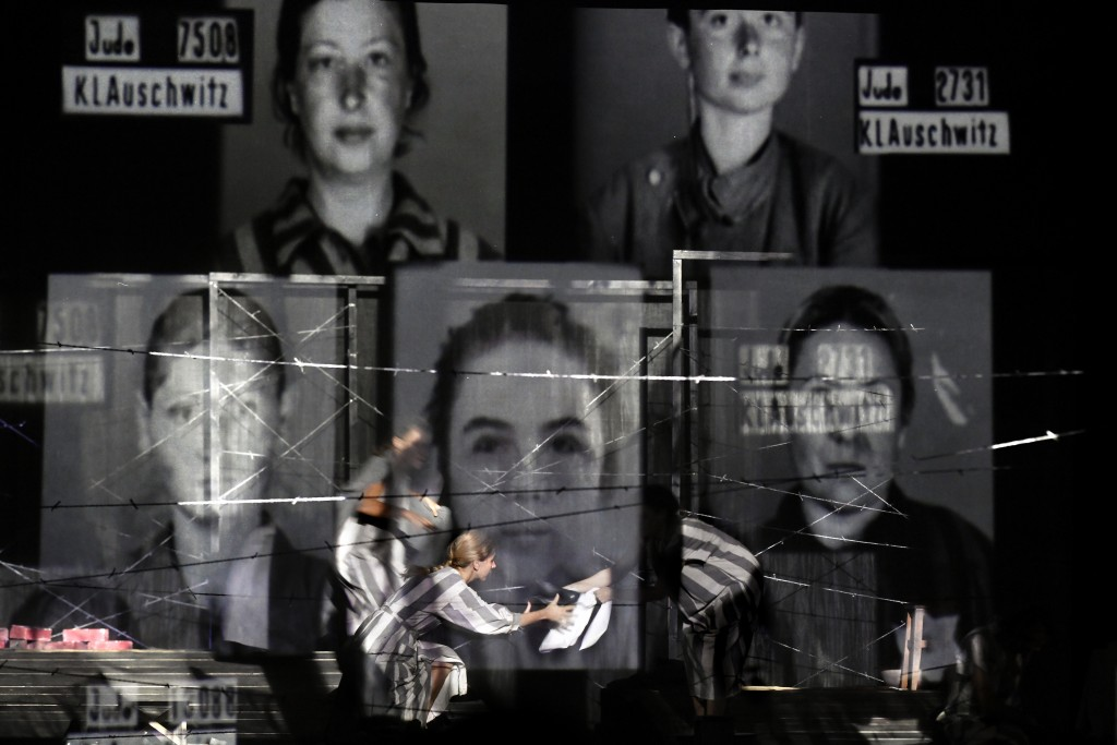 "Portraits of Auschwitz death camp prisoners are displayed on a mesh as actresses of the Jewish State Theatre, perform during the premiere of the ""The ..."