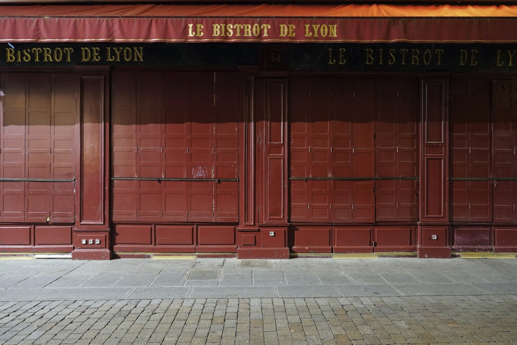A closed restaurant is pictured after the start of the curfew in the empty center of Lyon, central France, Saturday, Oct. 17, 2020. France is deployin...