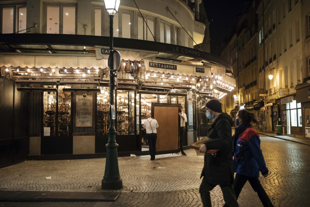 Waiters close a bar terrace in Paris, Saturday, Oct. 17, 2020. French restaurants, cinemas and theaters are trying to figure out how to survive a new ...
