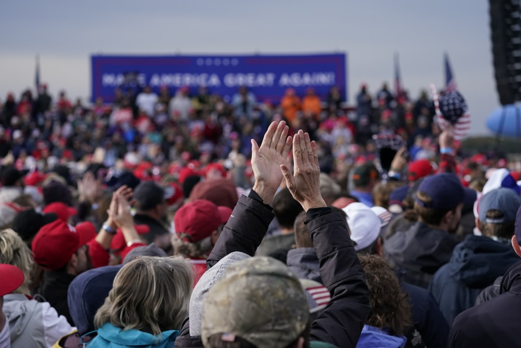 Supporters of President Donald Trump cheer as he speaks during a campaign rally at Muskegon County Airport, Saturday, Oct. 17, 2020, in Norton Shores,...