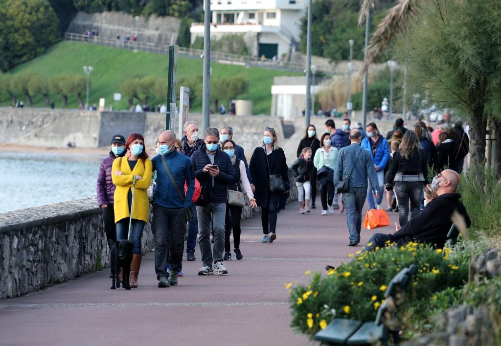 People wearing masks to protect against coronavirus, walk, near the Atlantic Ocean in Saint Jean de Luz, southwestern France, Saturday Oct. 17, 2020. ...