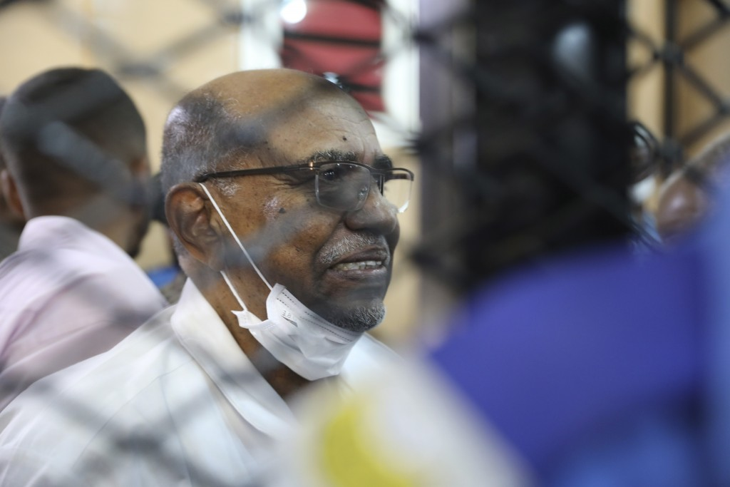 FILE - In this Sept. 15, 2020 file photo, Sudan's ousted president Omar al-Bashir sits at the defendant's cage during his trial a courthouse in Kharto...