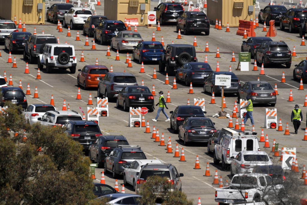 FILE - In this July 14, 2020, file photo, people wait in line for coronavirus testing at Dodger Stadium in Los Angeles. After months of struggling to ...