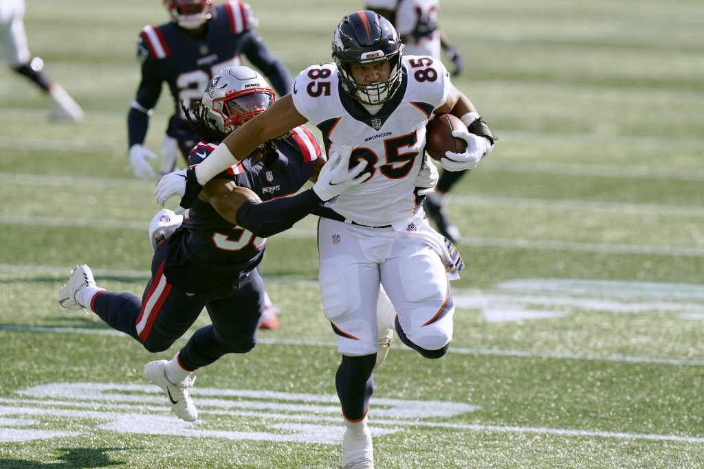 Denver Broncos tight end Albert Okwuegbunam (85) tries to run away from New England Patriots defensive back Kyle Dugger, left, after catching a pass i...