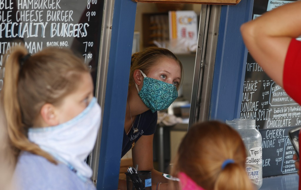 FILE - In this Aug. 4, 2020 file photo, a staffer wears a mask while taking orders at a small restaurant in Grand Lake, Colo., amid the coronavirus pa...