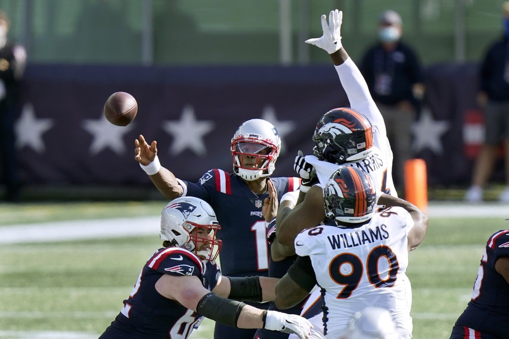 New England Patriots quarterback Cam Newton (1) passes under pressure from Denver Broncos defenders Shelby Harris, right rear, and DeShawn Williams (9...