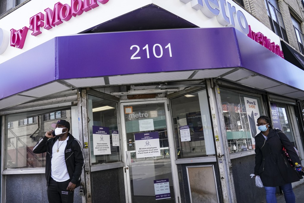 Pedestrians in masks pass a storefront on Thursday, Oct. 15, 2020, as restrictions are imposed on the area due to an increase in COVID-19 infections i...