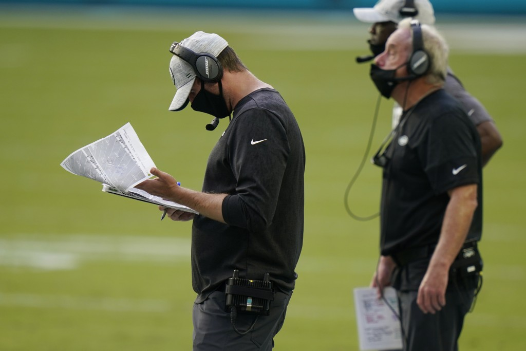 New York Jets head coach Adam Gase looks at copies of plays during the first half of an NFL football game against the Miami Dolphins, Sunday, Oct. 18,...