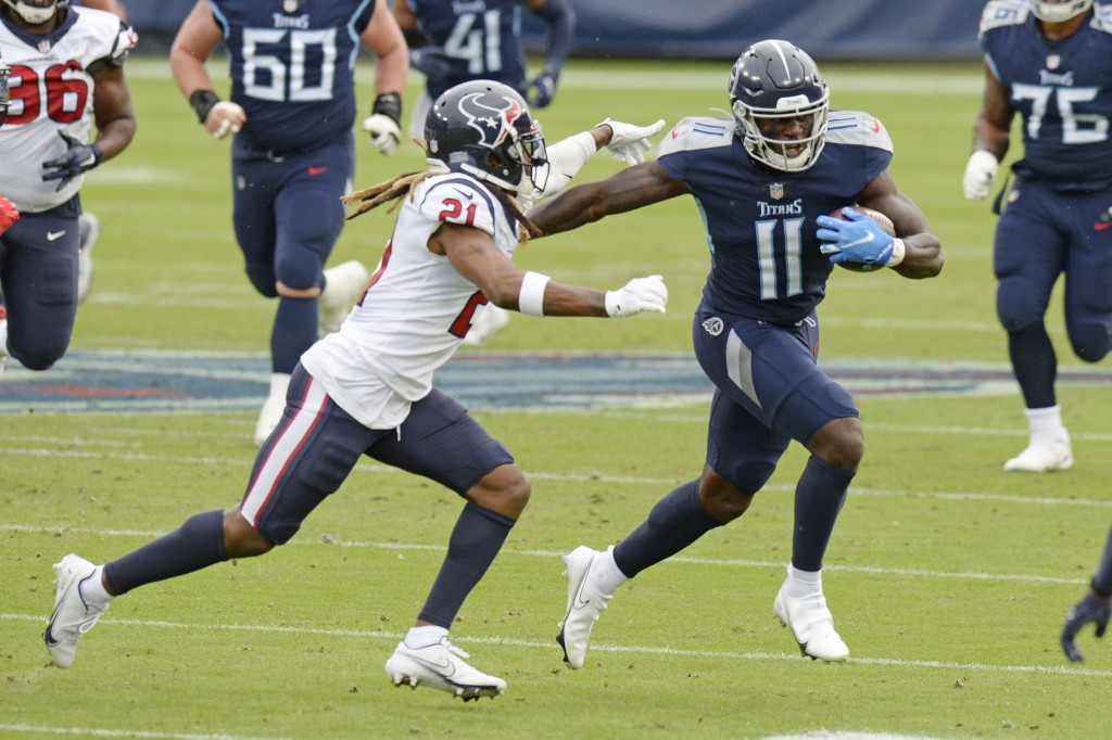 Tennessee Titans wide receiver A.J. Brown (11) is chased by Houston Texans cornerback Bradley Roby (21) in the first half of an NFL football game Sund...