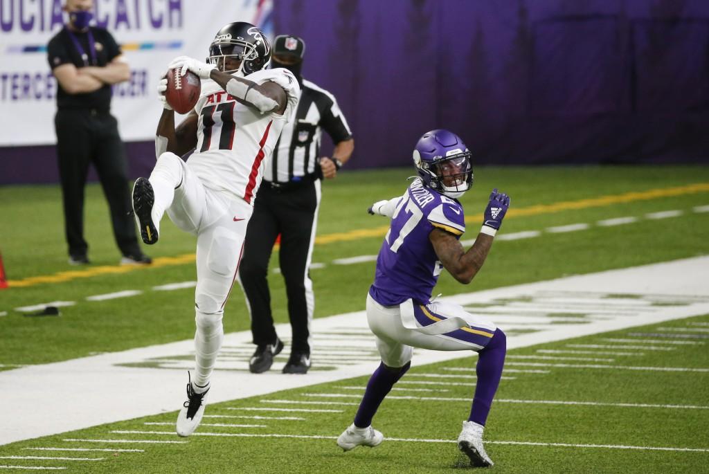 Atlanta Falcons wide receiver Julio Jones (11) catches a pass over Minnesota Vikings cornerback Cameron Dantzler during the second half of an NFL foot...