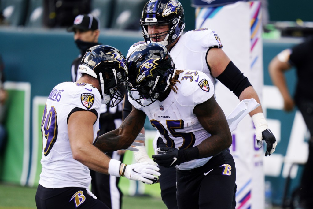 Baltimore Ravens' Gus Edwards (35) celebrates with Mark Andrews (89) after scoring a touchdown during the first half of an NFL football game against t...