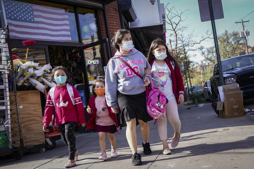 Pedestrians in masks pass a store on Thursday, Oct. 15, 2020, as government restrictions on business activity limit operations due to an increase of C...