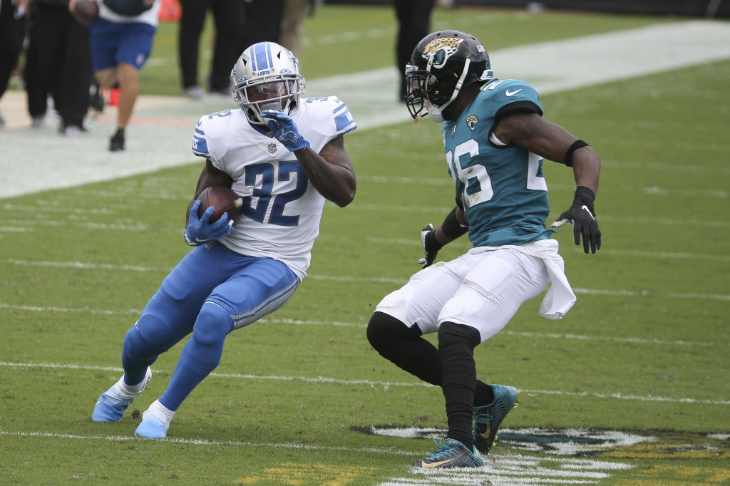 Detroit Lions running back D'Andre Swift (32) tries to avoid a tackle by Jacksonville Jaguars safety Jarrod Wilson, right, during the first half of an...