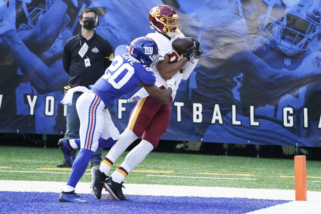 Washington Football Team's Logan Thomas (82) catches a pass for a touchdown in front of New York Giants' Julian Love (20) during the first half of an ...