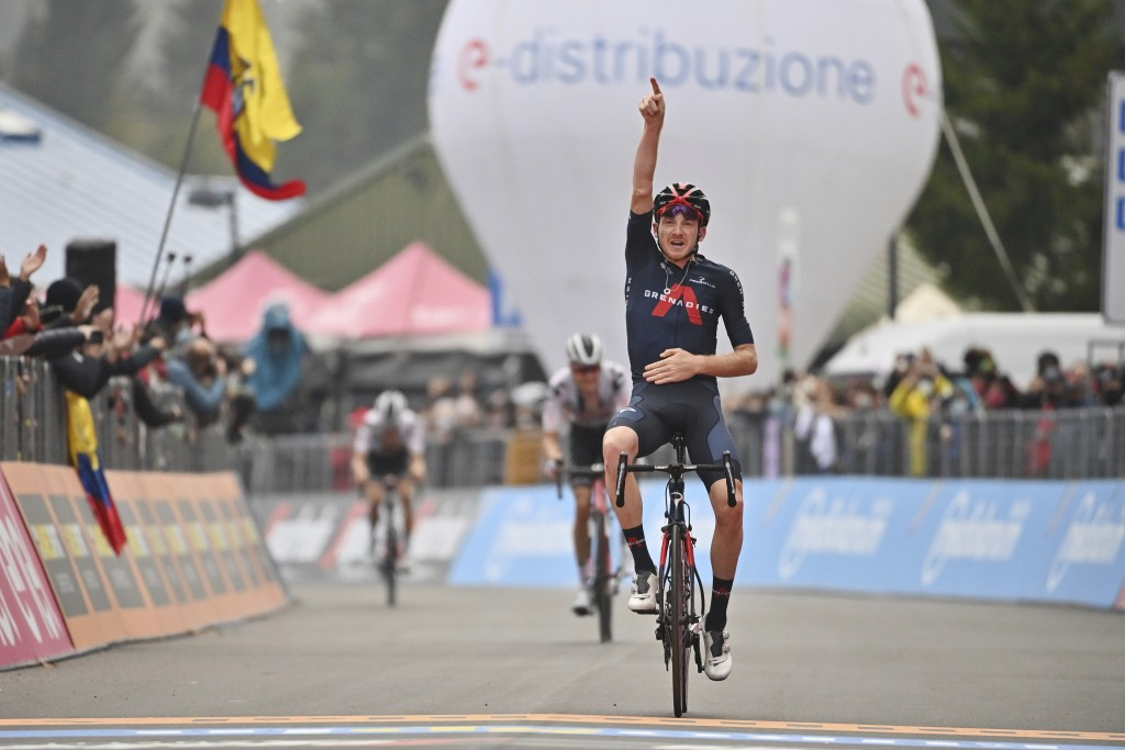 Britain's Tao Geoghegan Hart celebrates as he crosses the finish line to win the 15th stage of the Giro d'Italia cycling race, from Rivolto to Piancav...