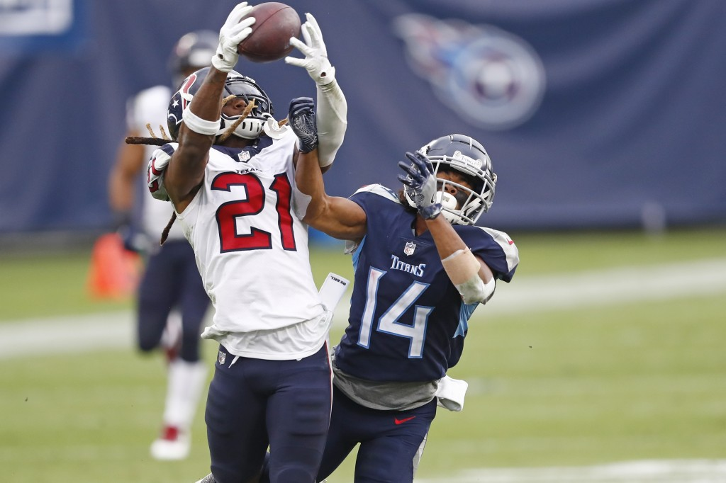 Houston Texans cornerback Bradley Roby (21) intercepts a pass intended for Tennessee Titans wide receiver Kalif Raymond (14) in the second half of an ...