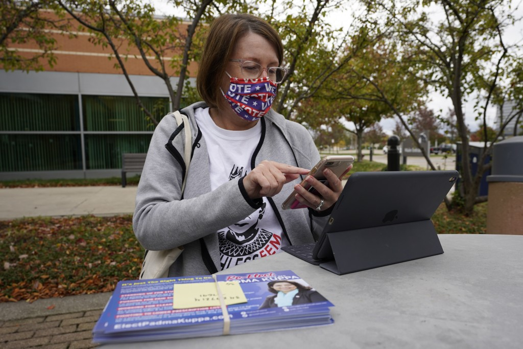 Julie Campbell-Bode, prepares to canvas for Democratic voters in Troy, Mich., Thursday, Oct. 15, 2020. In Michigan, women have cast nearly 56% of the ...