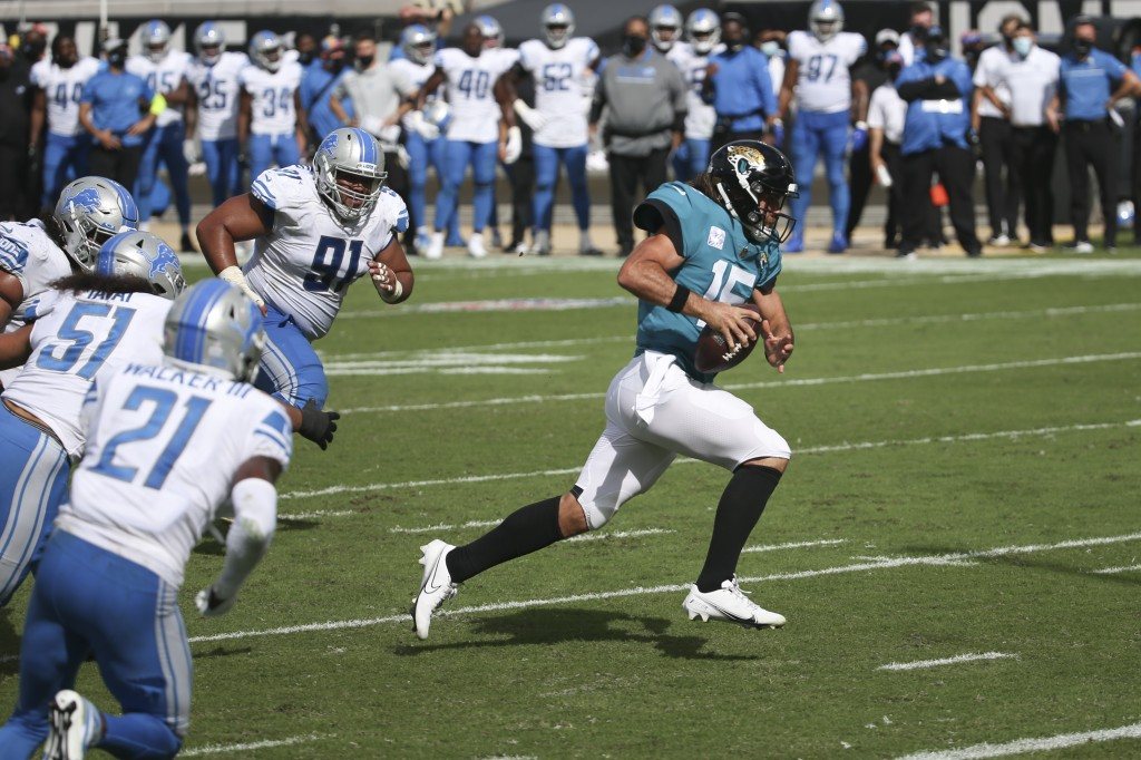 Jacksonville Jaguars quarterback Gardner Minshew II, right, scrambles past the Detroit Lions defense for a 6-yard touchdown during the second half of ...
