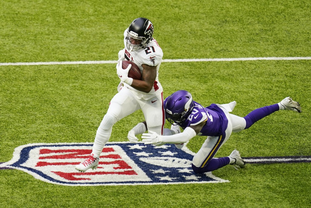 Atlanta Falcons running back Todd Gurley II (21) runs from Minnesota Vikings cornerback Jeff Gladney (20) during the first half of an NFL football gam...